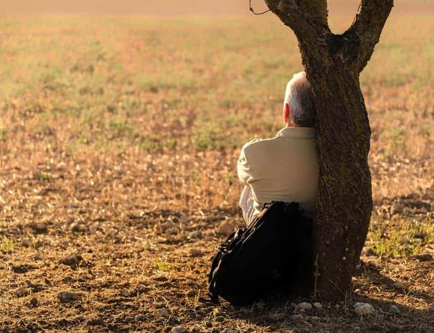Man sitting against a tree while thinking
